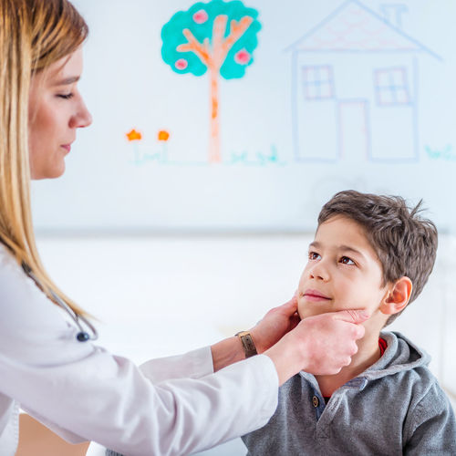 Pediatrician Examining Boy's Thyroid Glands Doctor  Pediatrician Medical Child Boy School Boy Thyroid Glands Touching Medicine Hospital Clinic Patient Health Kid Healthcare Care Childhood Female People Exam Professional Examination White Office Sick Adult Ilness Diagnosis Lifestyle Woman Examining Occupation Pediatric Specialist Examine Expertise Indoors  Pediatrist Visit Lab Coat Checking Checkup Two People