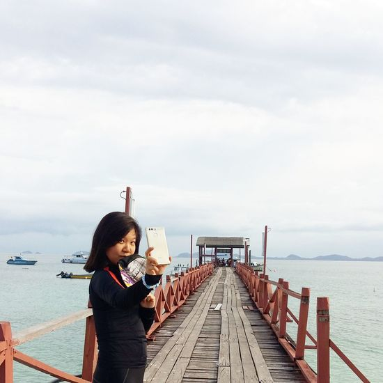 Young woman taking selfie while standing on pier against cloudy sky