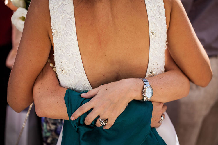 Midsection of newlywed couple embracing at wedding ceremony