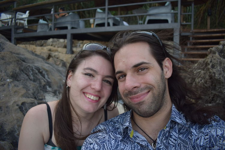 Portrait of smiling young couple sitting by rock outdoors