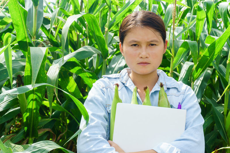 Young woman holding corn on field