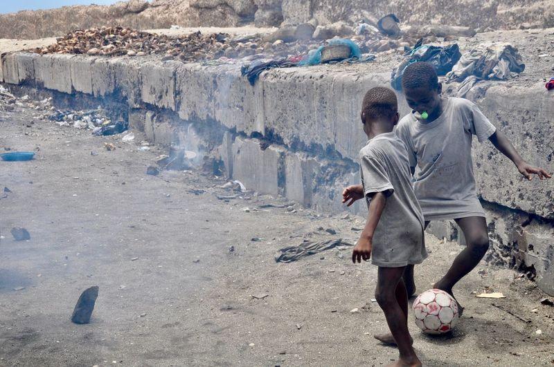 Boys playing soccer at beach