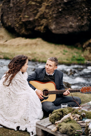 Man playing guitar while sitting with woman near river