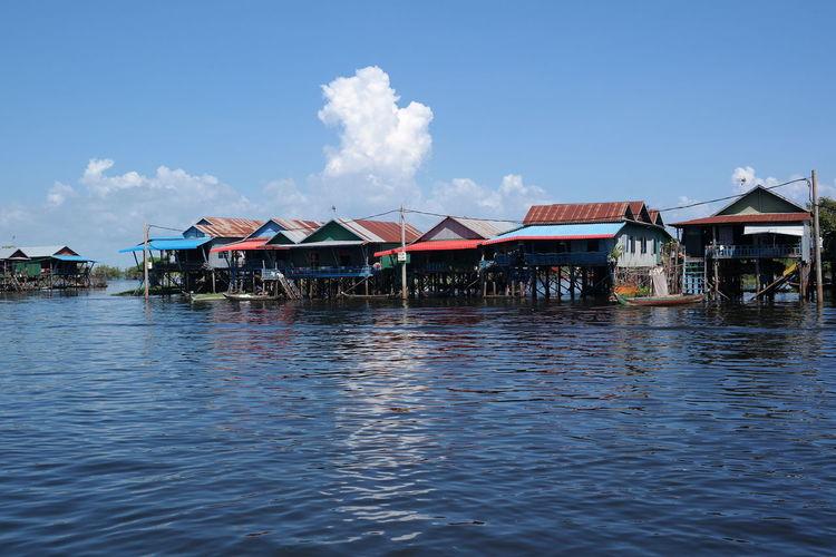 Stilt houses by buildings against blue sky