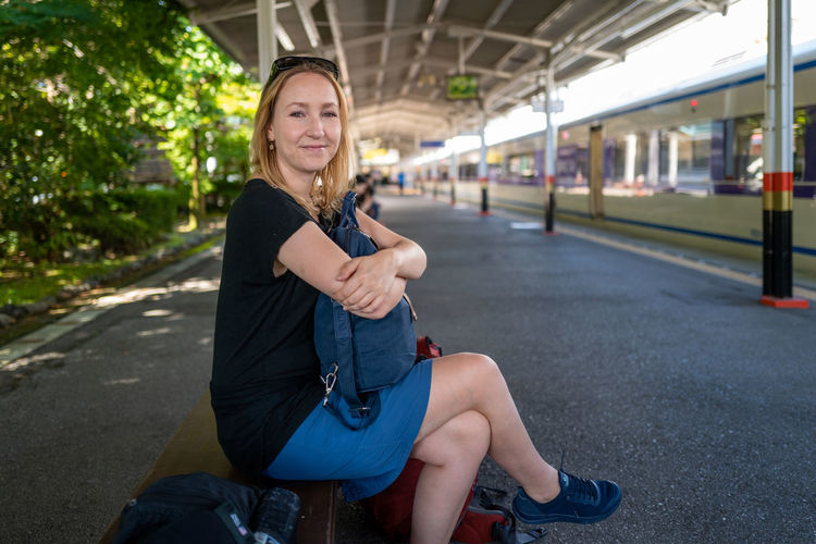 Portrait of smiling woman sitting on bench at railway station
