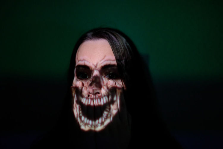 Close-up of spooky woman against green background