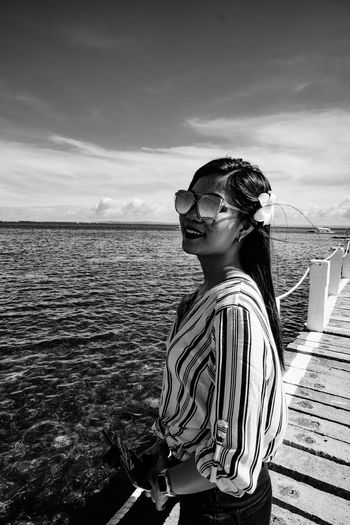 Young woman wearing sunglasses standing by sea against sky
