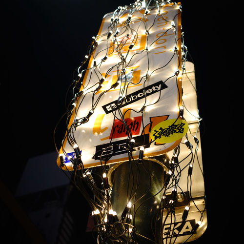 Low angle view of illuminated lanterns hanging over black background
