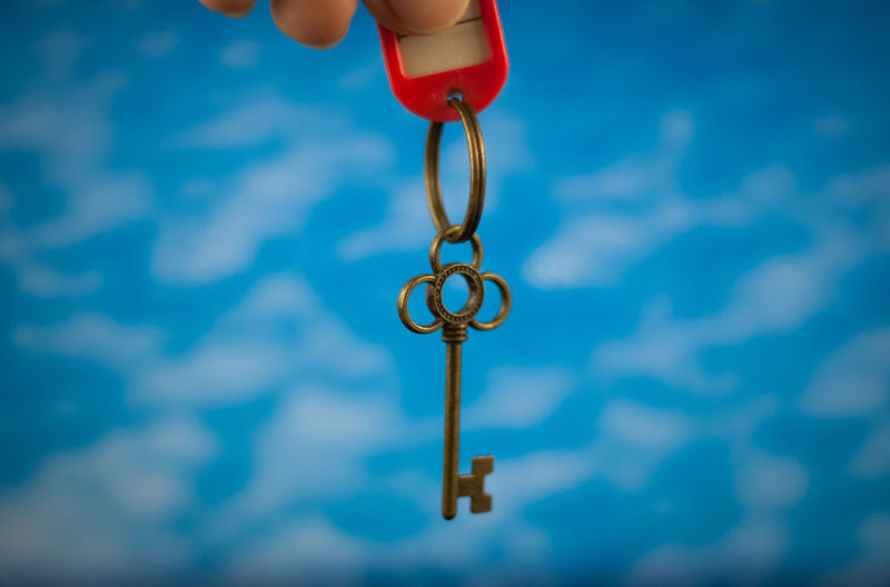 key house or key of success Blue Blue Background Body Part Business Finance And Industry Close-up Day Financial Finger Focus On Foreground Hand Holding House Human Body Part Human Hand Key Leisure Activity Lifestyles Metal Nature One Person Outdoors Real People Success Toy Unrecognizable Person
