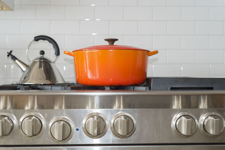 Close-Up Of Container On Gas Stove By Tiled Wall