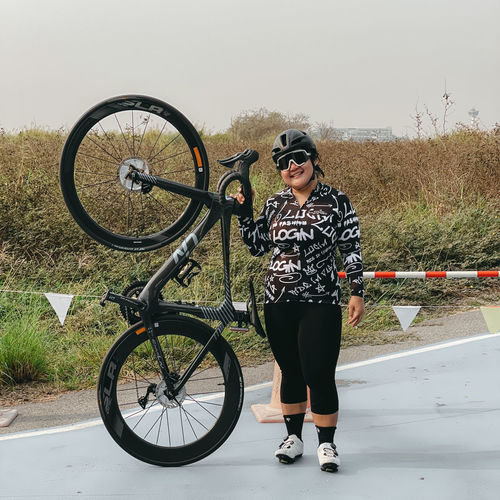 Full length of woman standing by bicycle