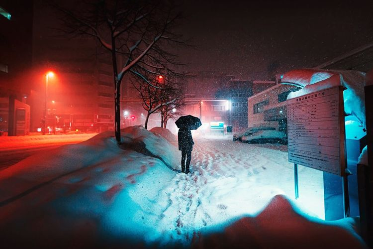 Man standing on snow covered road during snowfall at night