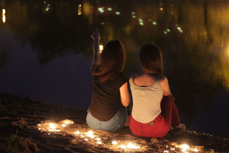 Rear view of female friends sitting by illuminated tea light candles at lakeshore during night