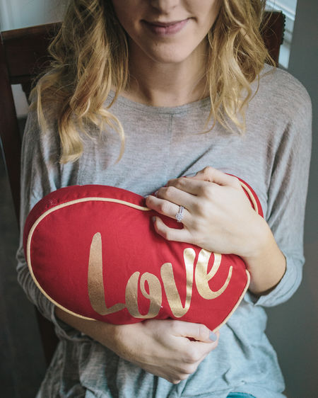 """Woman holding a red pillow shaped like a heart that says """"Love"""" for Valentines Day Love, Hearts, Valentines, Pillow, Red, Holding, Woman, Hands,"""
