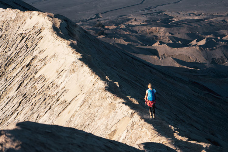 Rear view of woman walking on mountain during sunny day