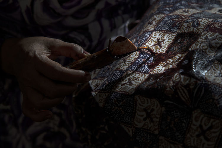Cropped hand of craftsperson making batik at workshop