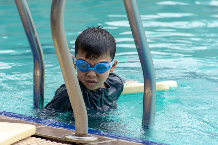 Asian boys are swimming in the pool. Childhood Child One Person Water Boys Leisure Activity Men Males  Real People Portrait Lifestyles Sea Day Looking At Camera Front View Headshot Nature Outdoors Innocence Swimming Pool Eyewear