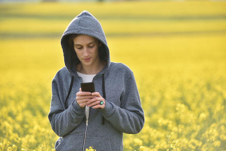 Young Woman Using Phone On Field