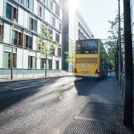 City bus driving down a road in center of Berlin, Germany, morning sun light reflection in building. Against The Sun Architecture Bus City City Life Day Diminishing Perspective Double Decker Bus Driving Early Modern Morning Morning Sun No People Public Transportation Reflection Residential Building Road Street Sunlight Sunny The Way Forward Yellow