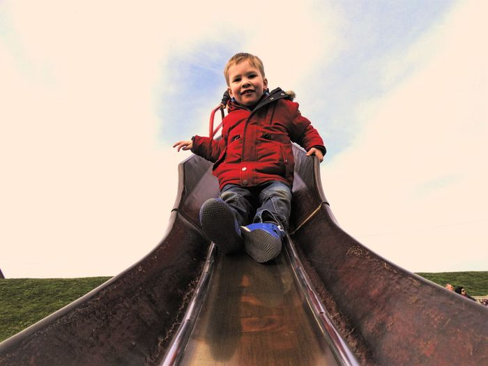 Low angle portrait of boy sliding on slide against cloudy sky