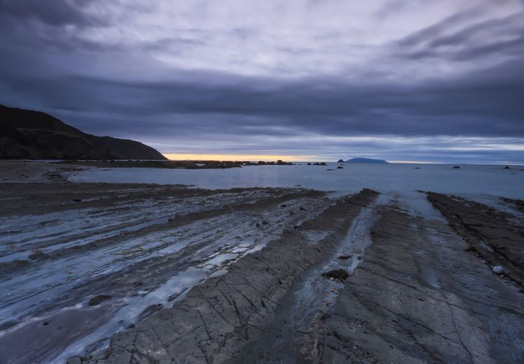 Cape colville against cloudy sky at sunset