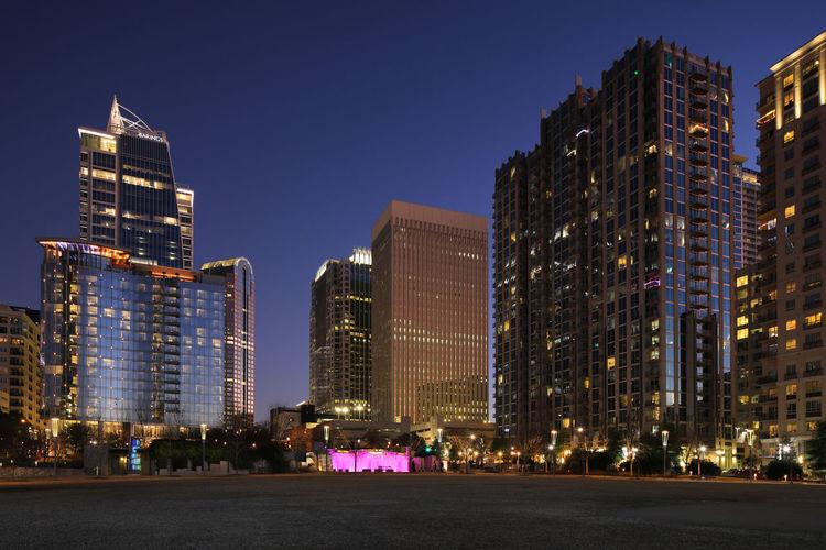 Illuminated city buildings against clear sky at dusk