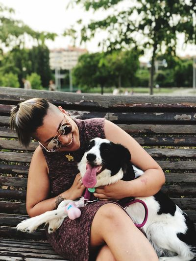 Smiling young woman sitting with border collie at park