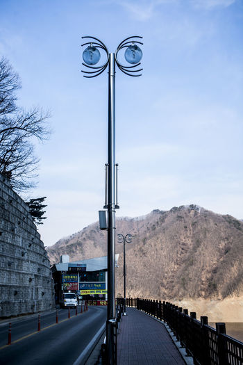 Street Light On Road By Mountain Against Sky