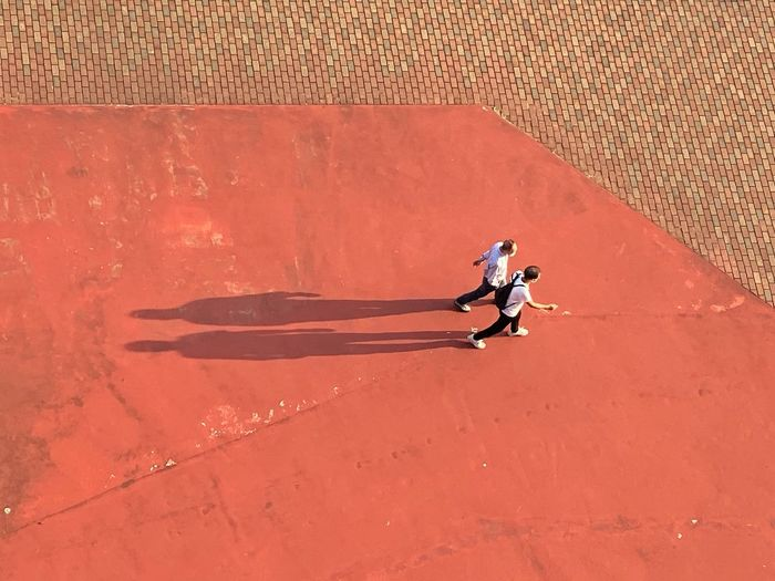 High angle view of woman walking on red wall