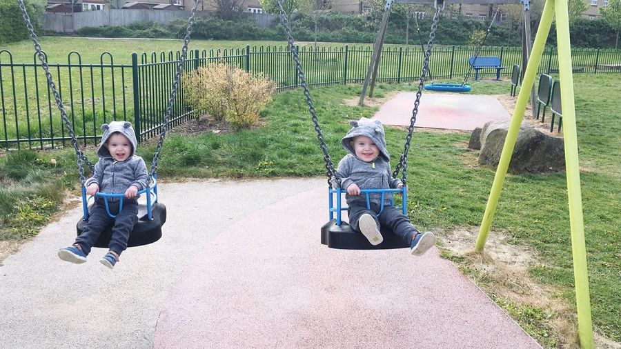 Portrait of cute boys sitting in swing at playground