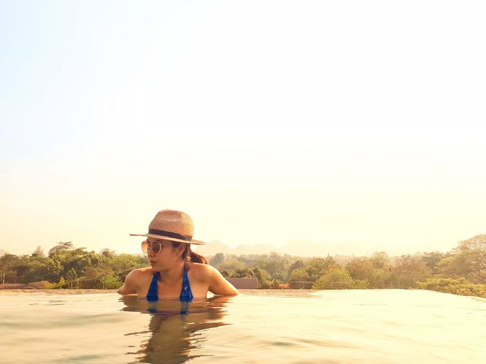 Woman wearing sunglasses and hat while swimming in infinity pool against sky during sunset