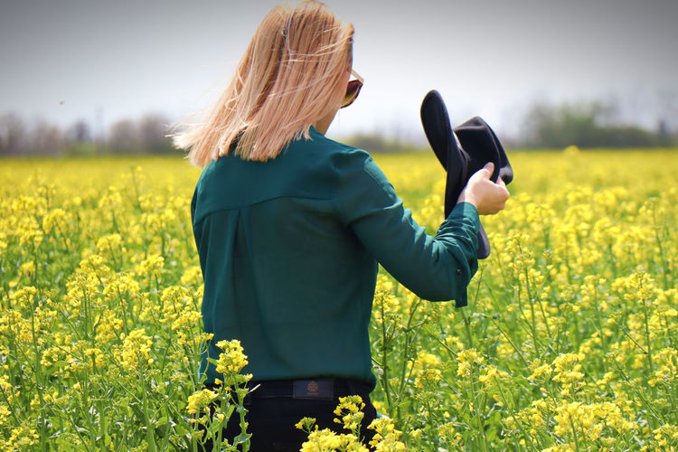 Rear view of woman standing by yellow flowers on field
