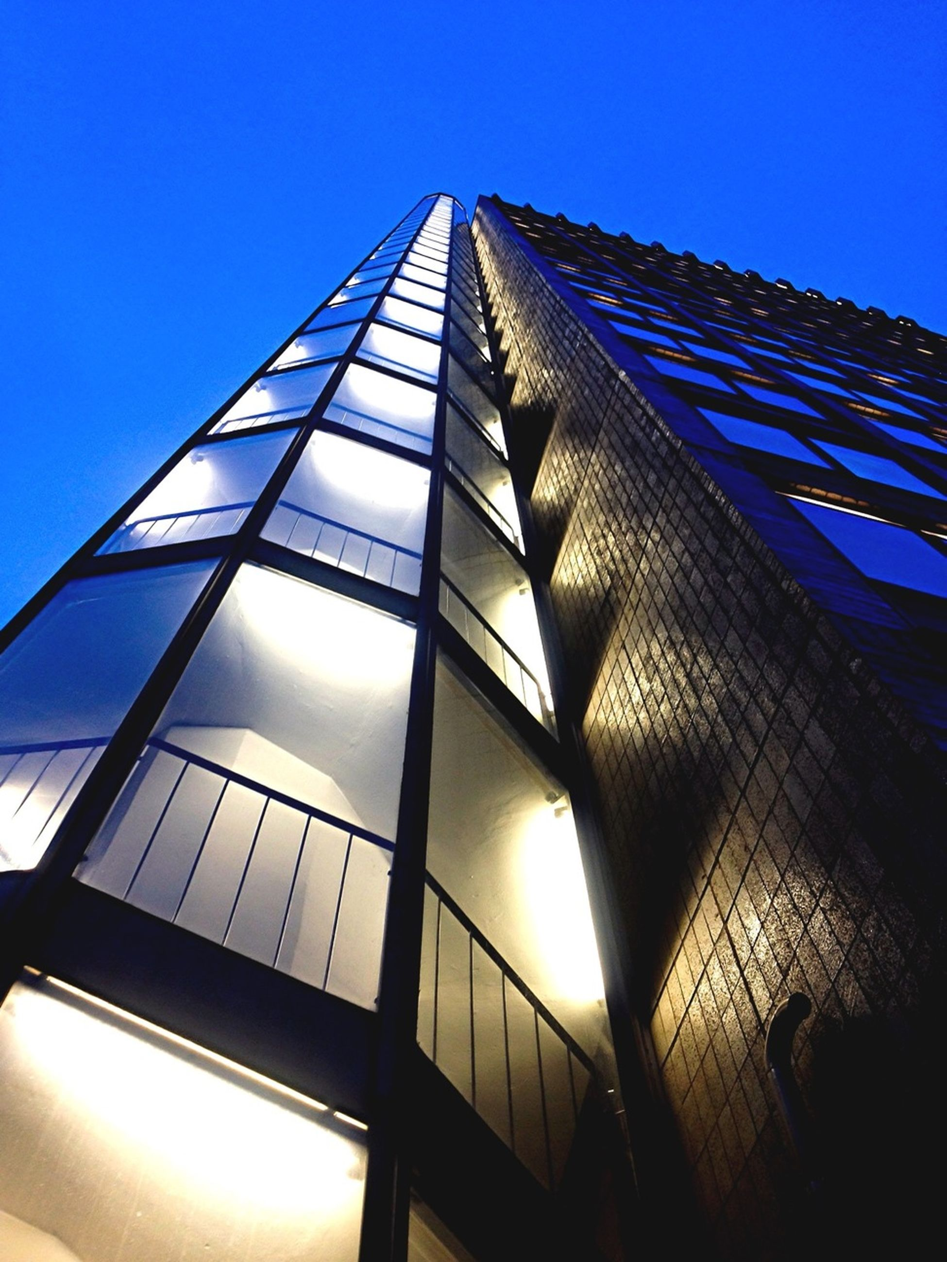 low angle view, architecture, built structure, building exterior, modern, clear sky, tall - high, office building, glass - material, skyscraper, sunlight, tower, sky, city, blue, building, sun, sunbeam, day, no people