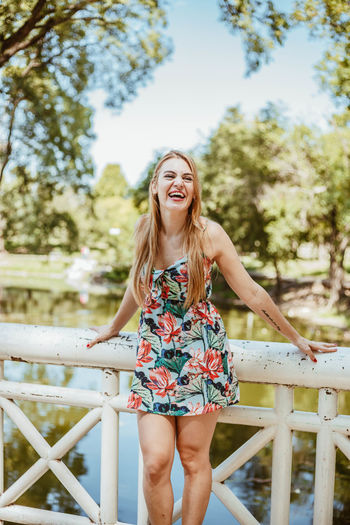 One Person Lifestyles Three Quarter Length Hair Looking At Camera Casual Clothing Hairstyle Blond Hair Beautiful Woman Flower Dress Beautiful Dress  Country Lake Park Trees Sunny Day Smiling Summer Laughing Hat Female Model Exterior Fashion Photography