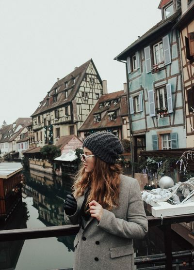 Young woman standing on bridge over river against buildings