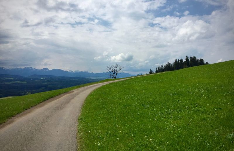 Road Passing Through Grassy Field Against Cloudy Sky