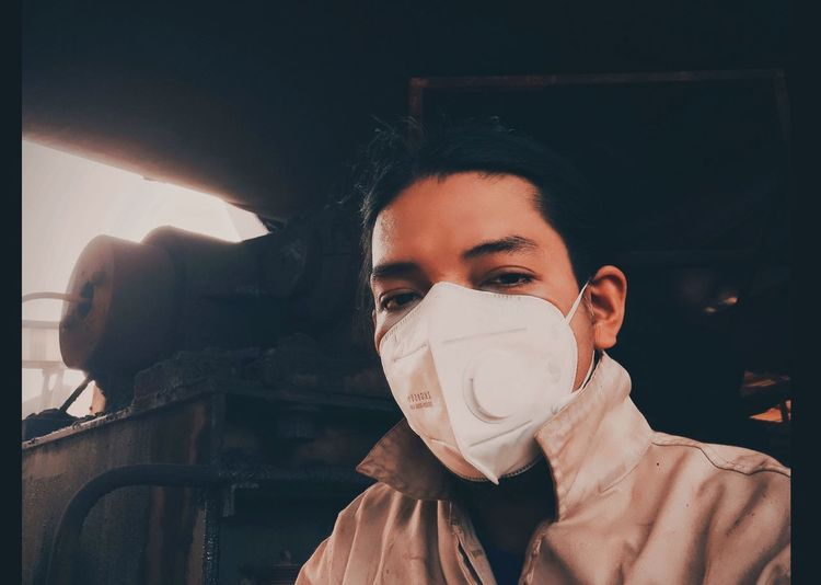 A man posing wearing a mask under an industrial machine in the afternoon