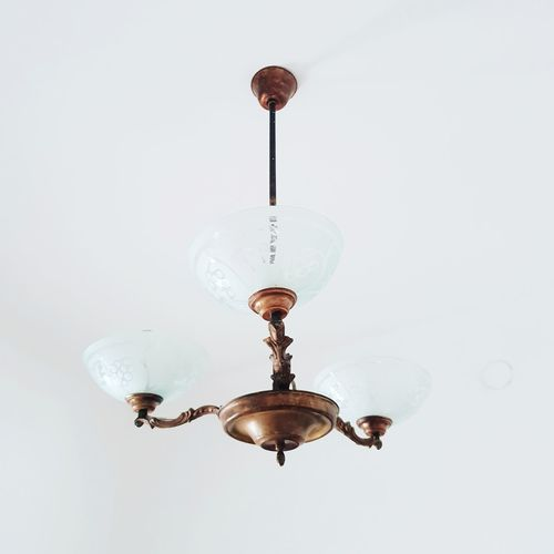 Low angle view of illuminated pendant light hanging on ceiling