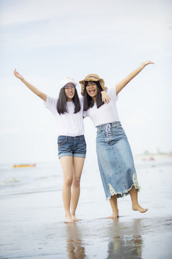 Full length of happy friends standing at beach against sky