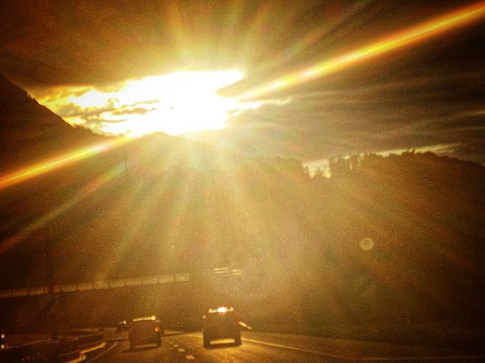 Cars on road in city against bright sun