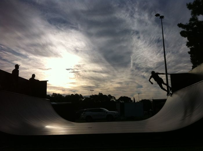 Silhouette of cars against cloudy sky