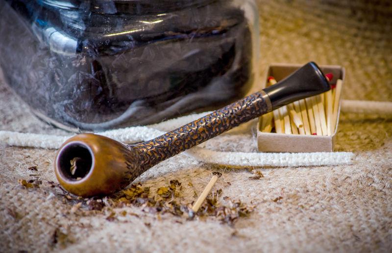 Close-up of smoking pipe on burlap
