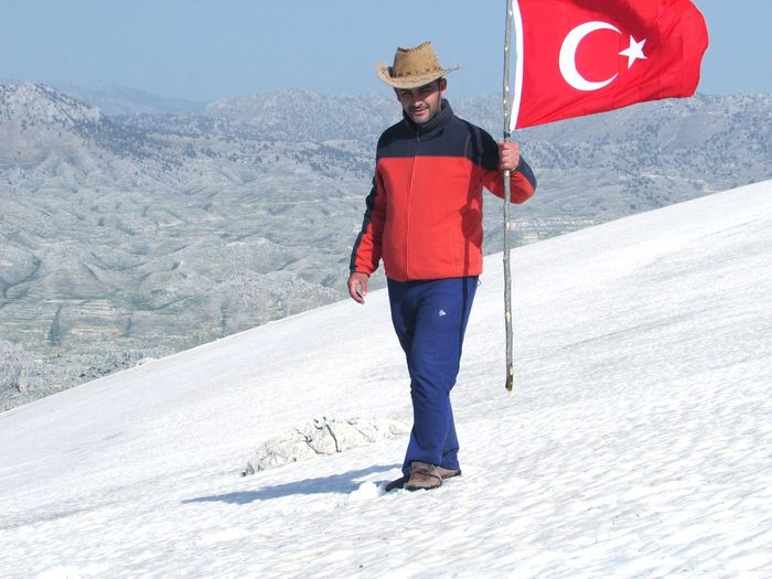 Full length of man standing on mountain road during winter