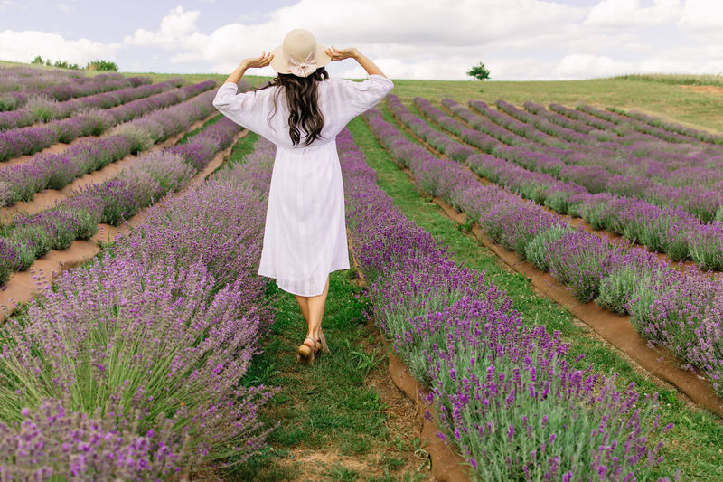 Close up of beautiful smiling woman in hat enjoying summer in lavender field