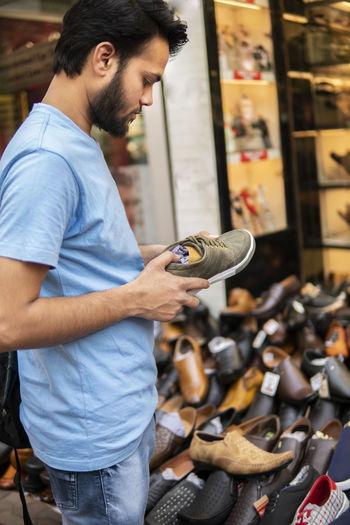 Man choosing shoes in market