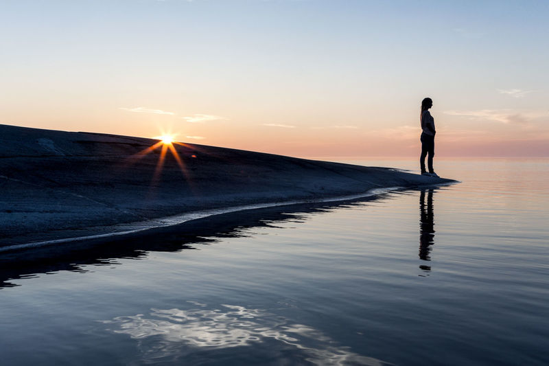 Silhouette woman standing in water against sky during sunset