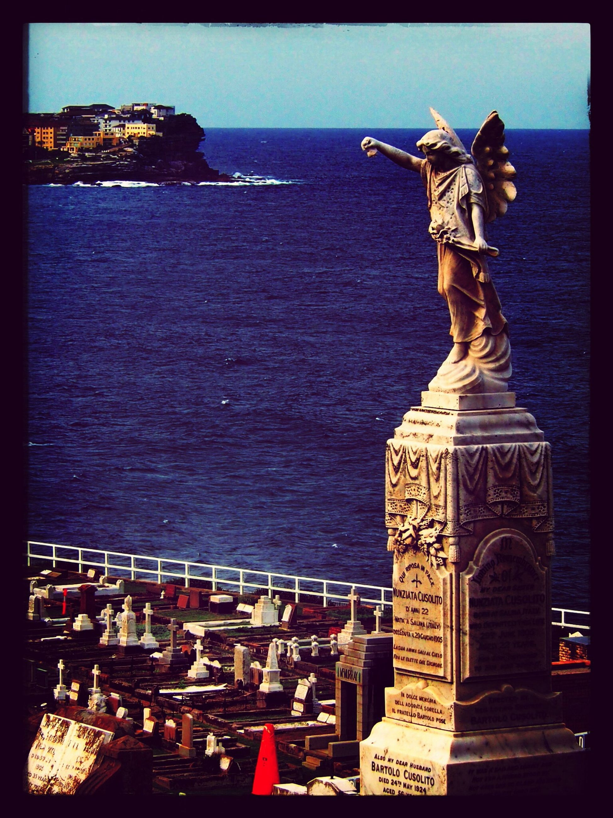 sea, water, human representation, sculpture, art and craft, horizon over water, statue, art, creativity, clear sky, sky, travel destinations, built structure, transfer print, blue, animal representation, architecture, auto post production filter, tourism