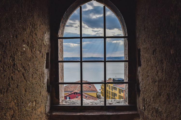 Houses By Sea Against Cloudy Sky Seen Through Window Of Old Building