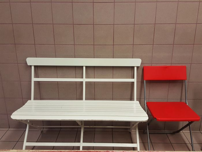 Bench and chair against tiled wall