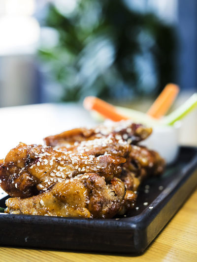 Close-up of chicken wings with sesame seeds served in plate on table